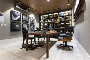 Mesa e teto em madeira destacam ambiente sóbrio do escritório