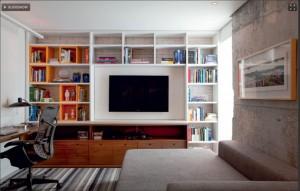 A estante ganhou caixas cor-de-laranja para a sala/escritório do apartamento de 96 m²