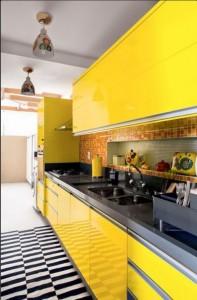 Armários com laca amarela predominam no ambiente da cozinha, contrastando com o piso zebrado.