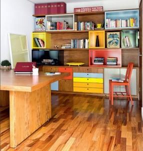 Estante com módulos coloridos encaixados entre as prateleiras com 3 cm de espessura. Os diferentes tons da laca aplicada nas peças ajudam a identificar os livros, separados por temas.