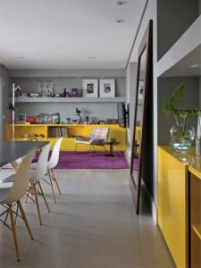 Neste apartamento, todos os armários são amarelos. Funcionando como aparador e bar, um móvel no mesmo tom chama a atenção no living integrado à sala de jantar.